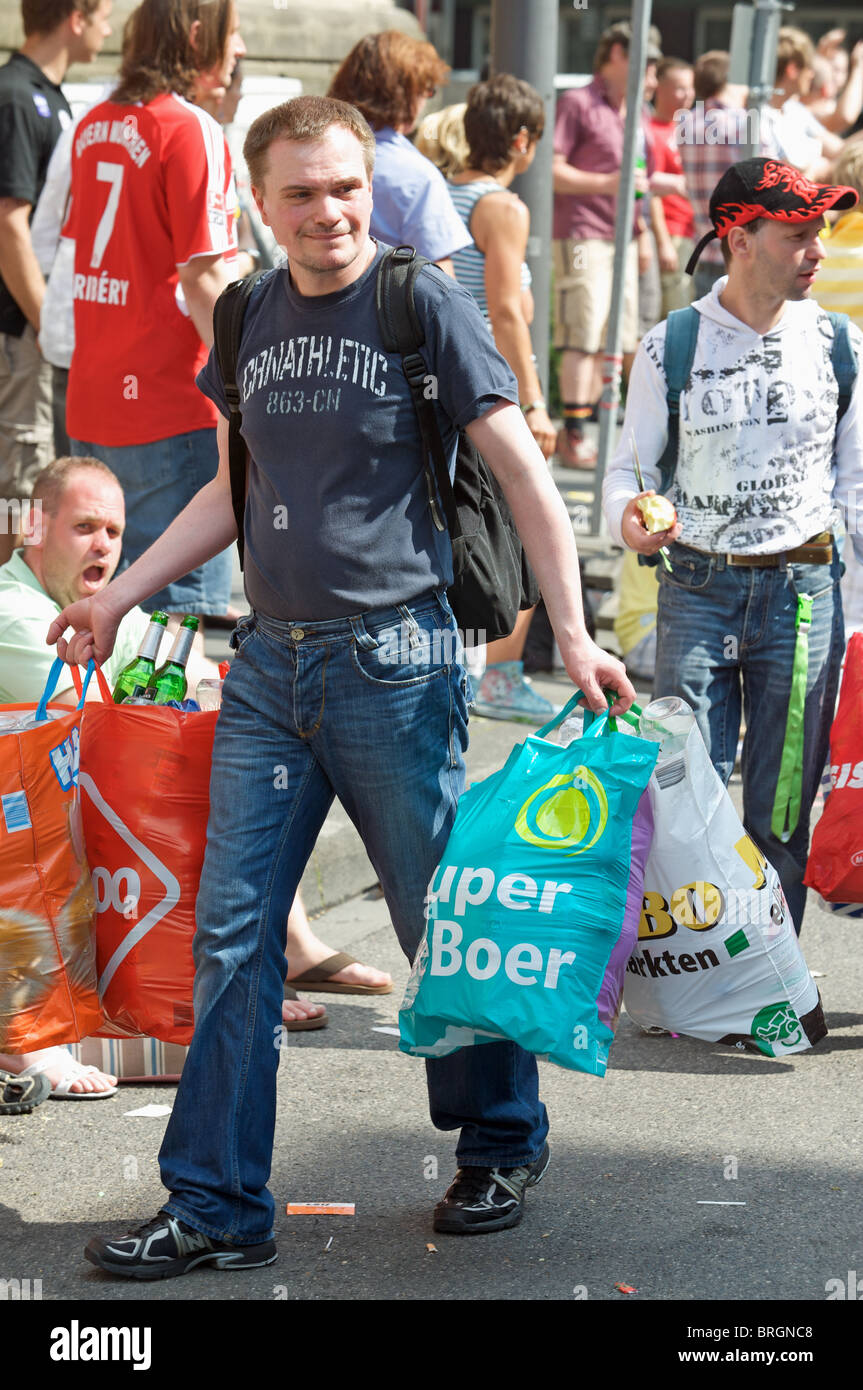 Jobless man collecting glass bottles after a street fair, Cologne, Germany. - Stock Image