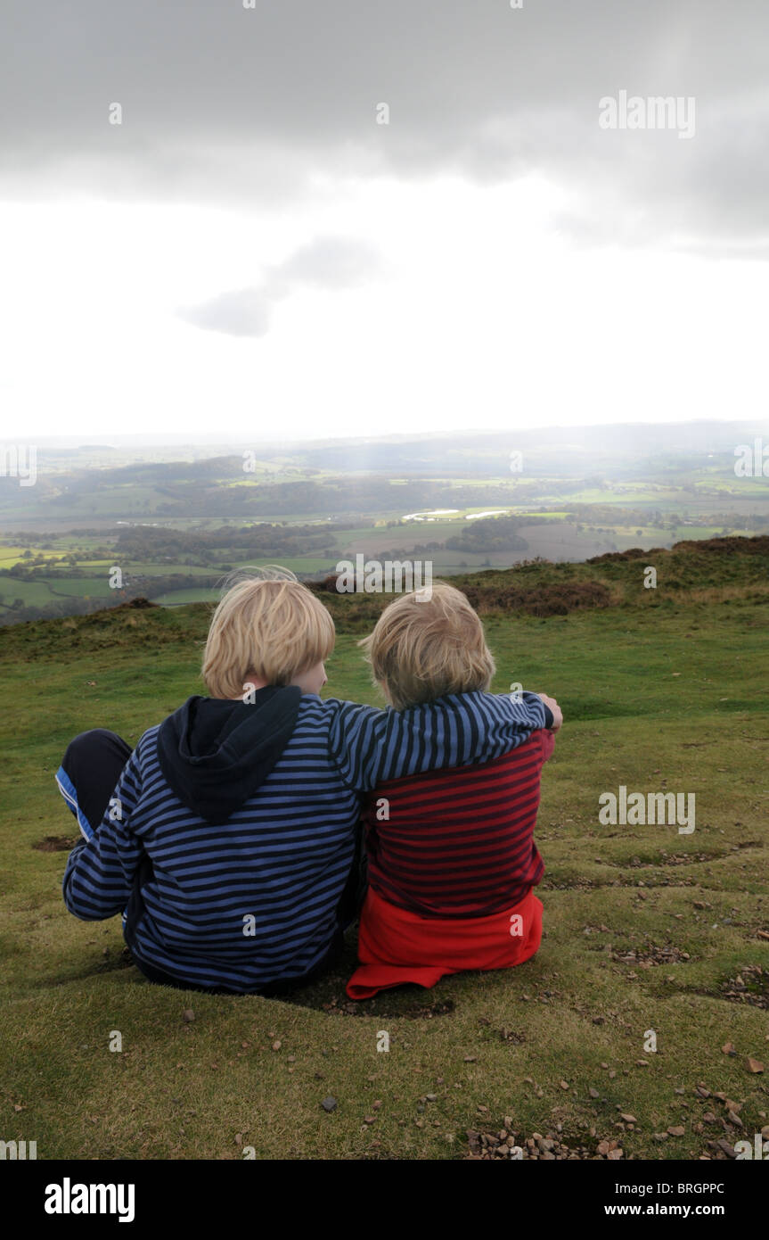 A boy comforts his young brother as they sit on the grass looking over a stormy landscape at the top of the Wrekin - Stock Image