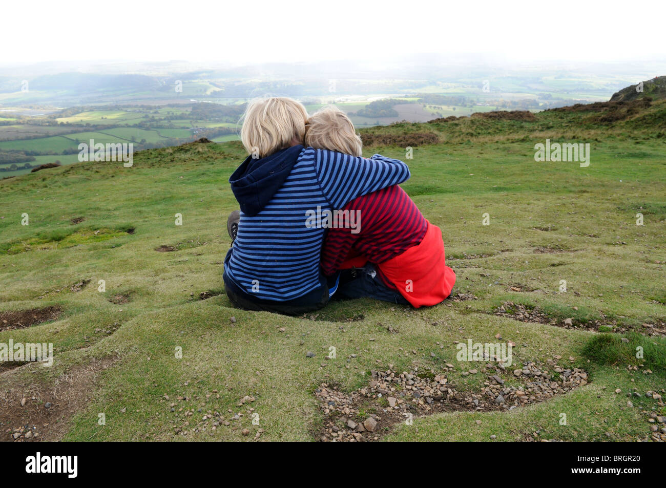 A boy comforts his young brother as they sit on the grass looking over hills from the top of the Wrekin in Shropshire - Stock Image