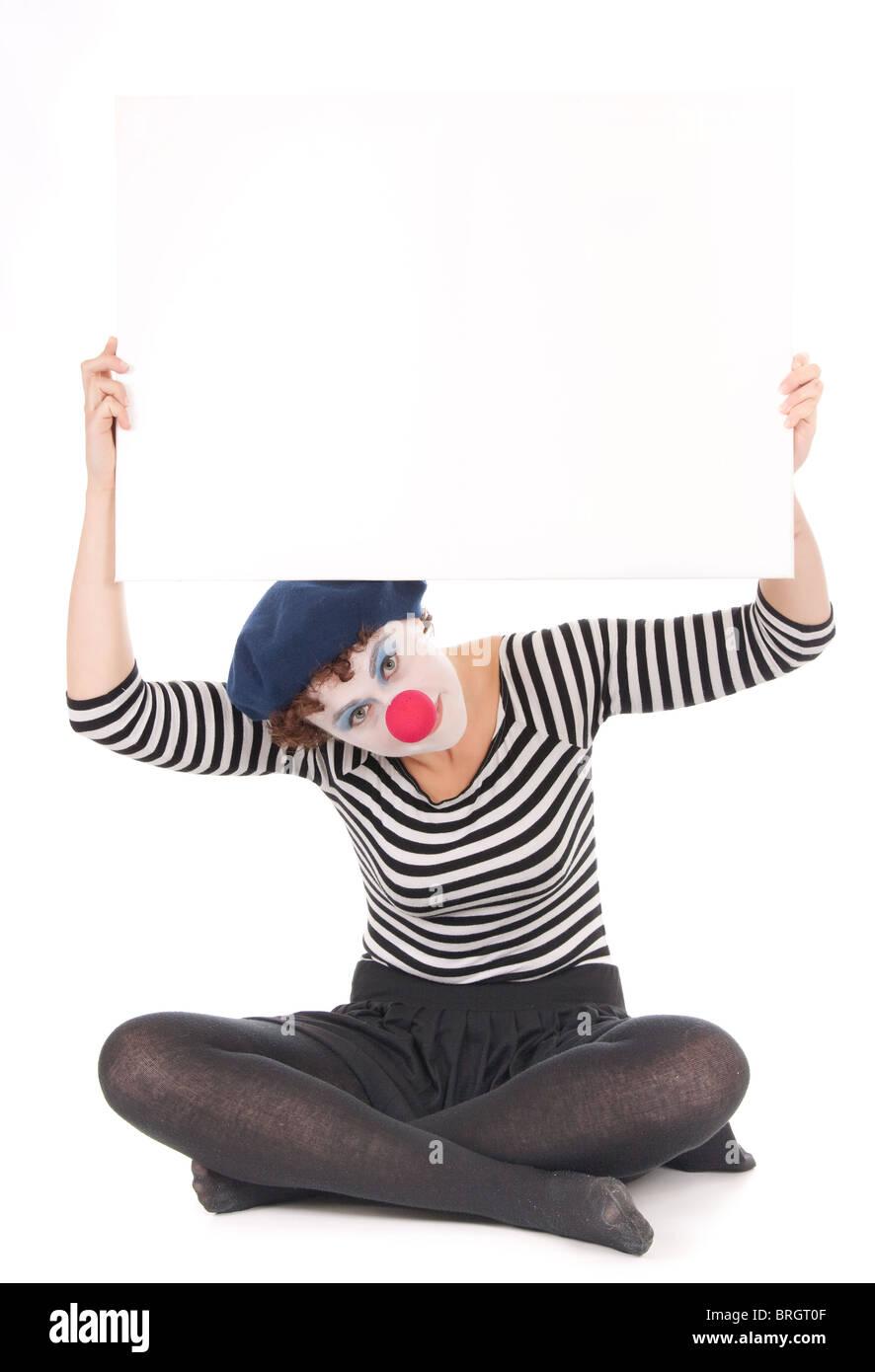 clown woman cross legged on floor holding blank billboard - Stock Image