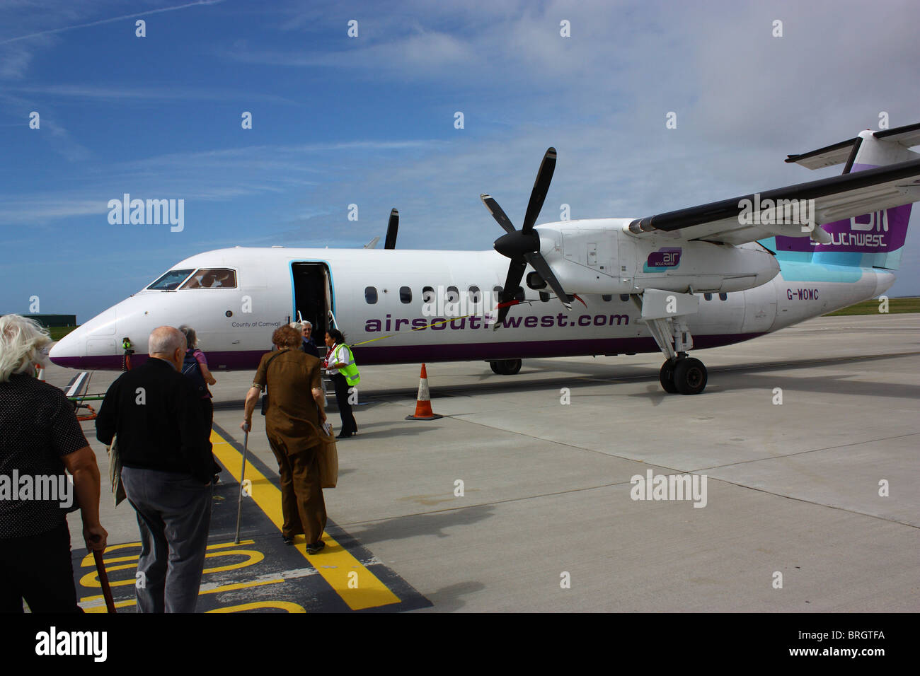 Passengers boarding a Dash 8 at Jersey Airport. Fine day, little wind and no rain. - Stock Image