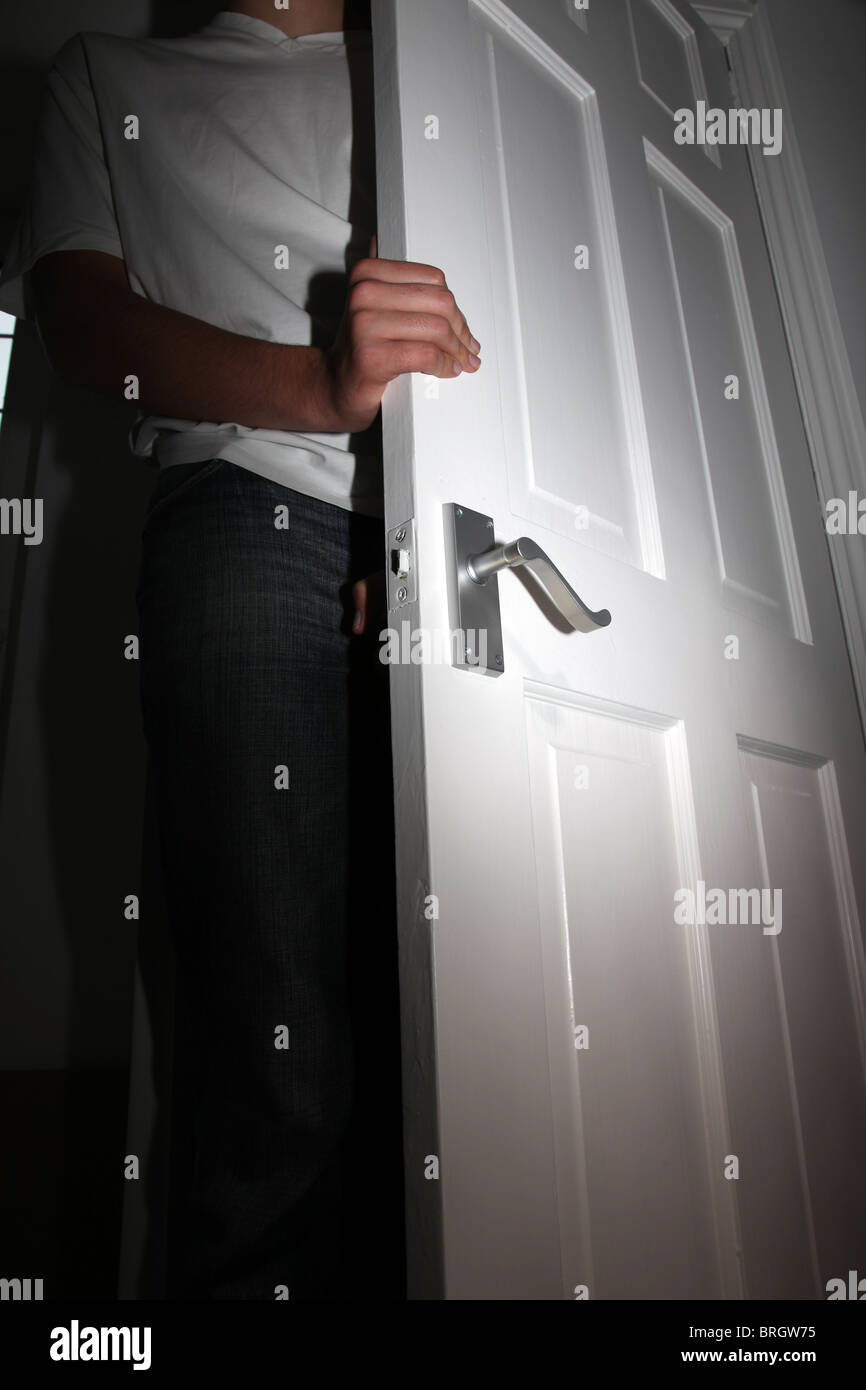 Open door with man entering a room. - Stock Image