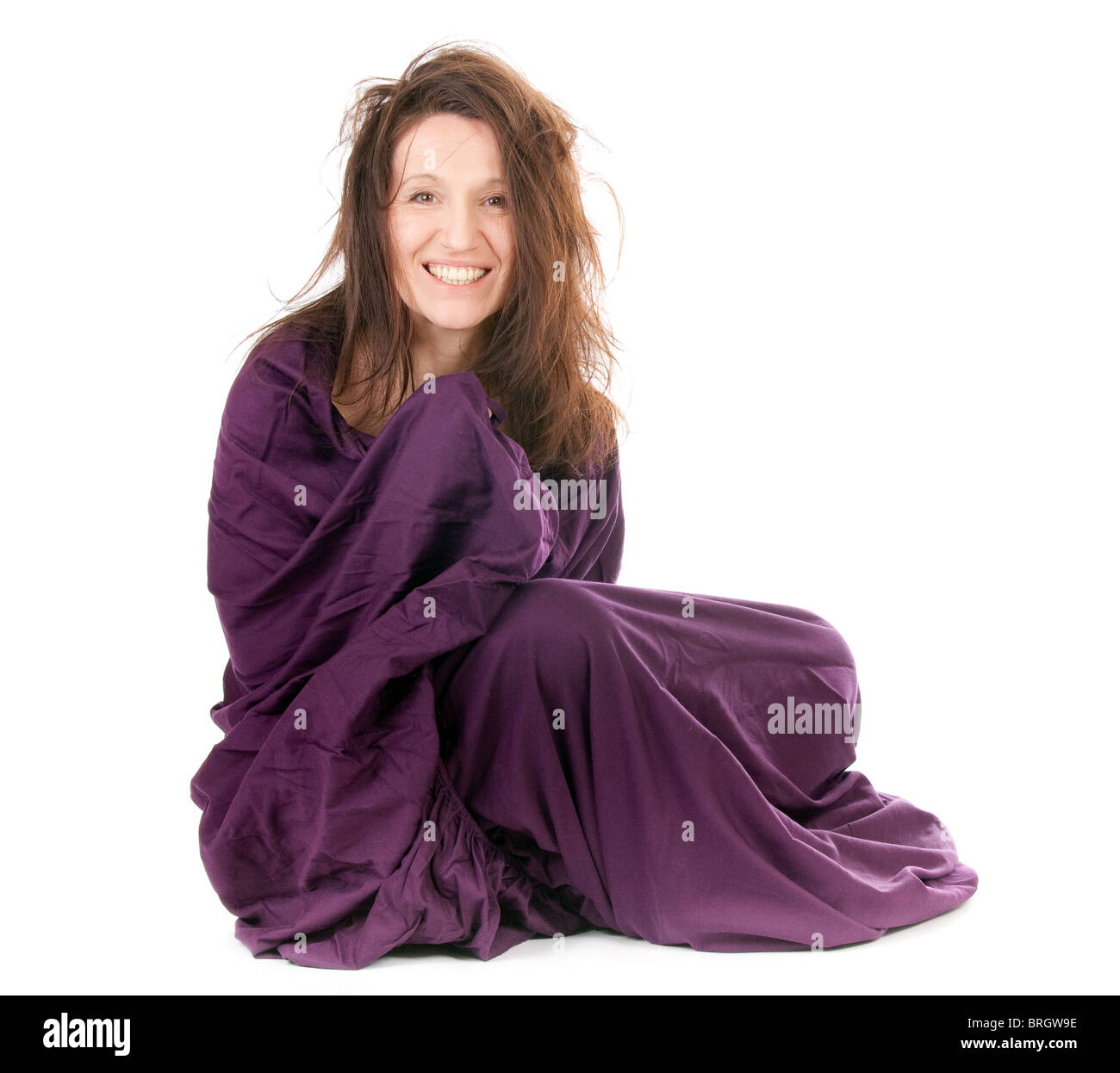 smiling beautiful mature woman wrapped in purple sheet isolated on white - Stock Image