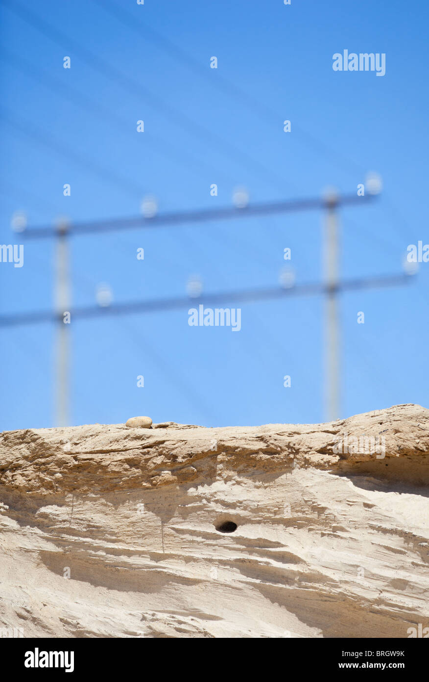 Sand Martin ( Riparia Riparia ) swallow nest hole on sandbank underneath power line - Stock Image