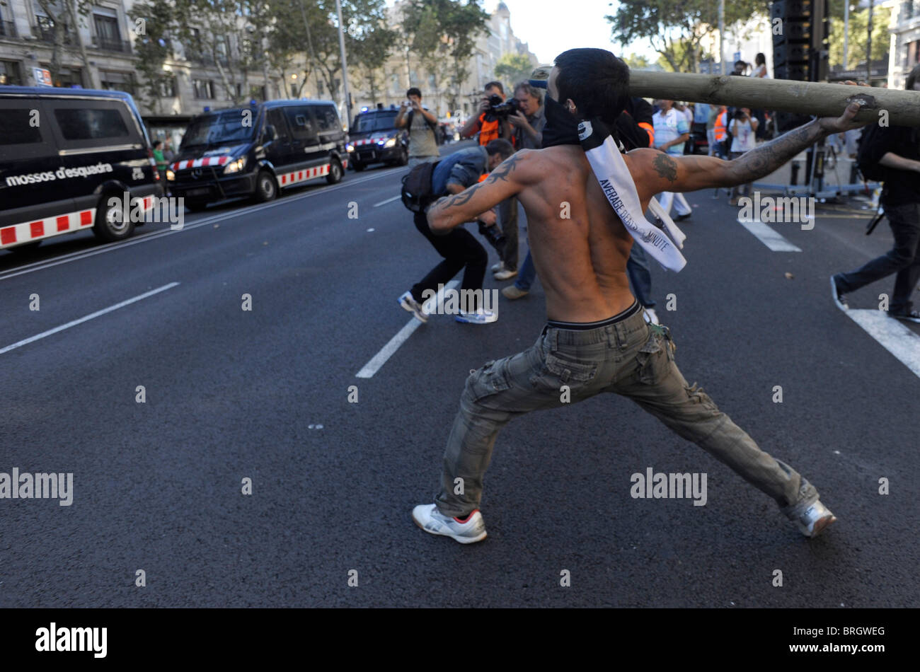 An activist anti system throws a stake against the police vans during during clashes in the general strike in Barcelona. - Stock Image
