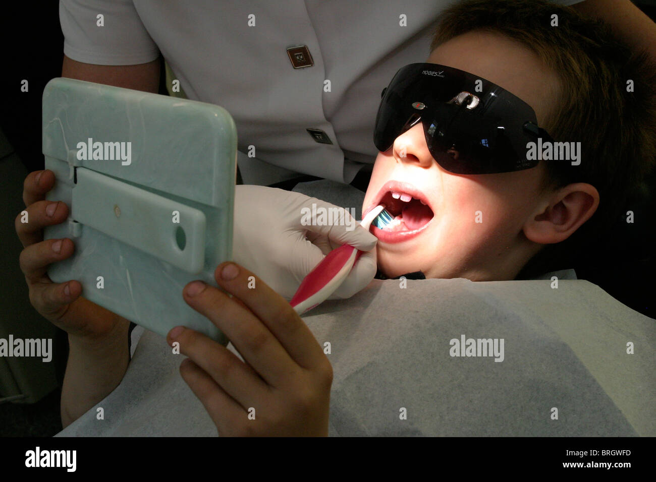 Young child having teeth inspected and taught basic hygiene and tooth dental care  by dentist - Stock Image