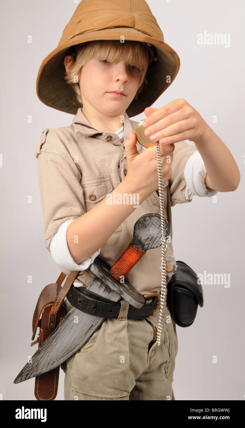 Young boy dressed up as a pretend Victorian explorer wearing a pith helmet  looks at his 0e677914c63