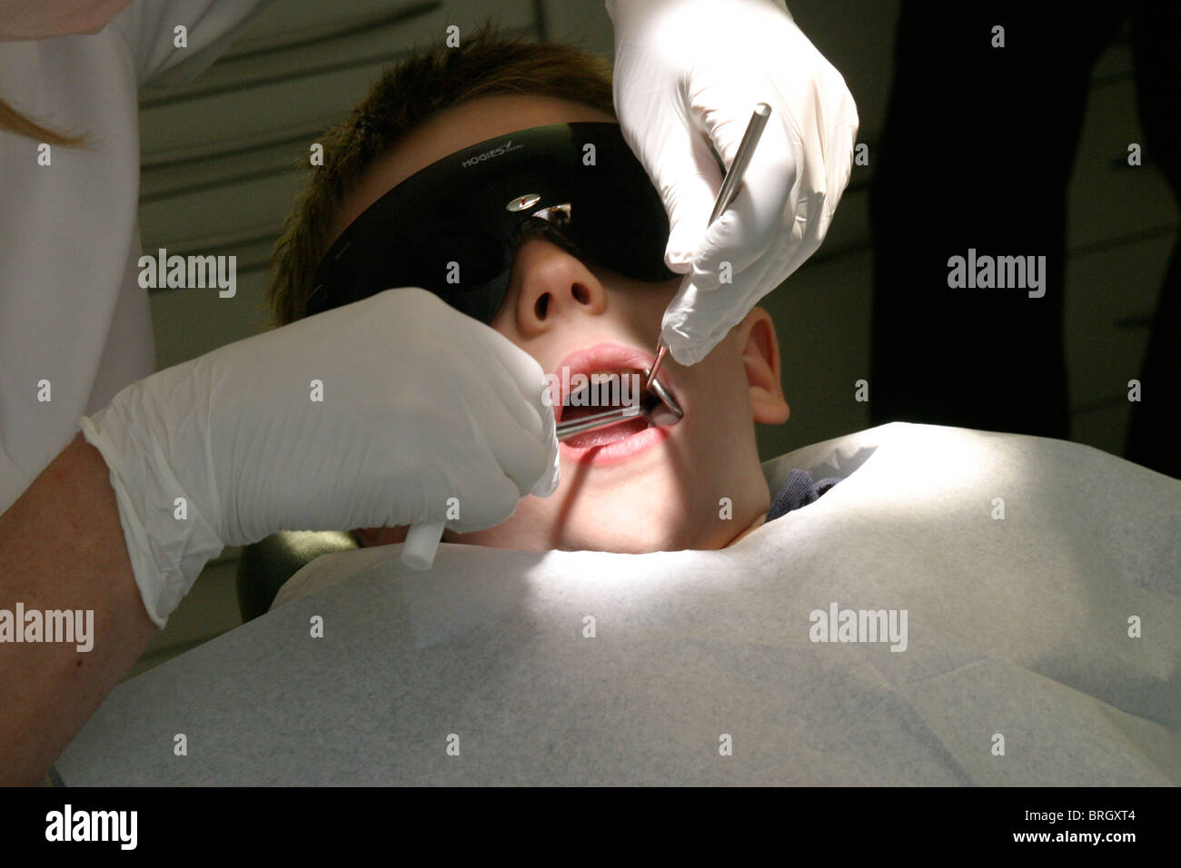 Young child having dental check-up  inspecting teeth and  checking hygiene - Stock Image