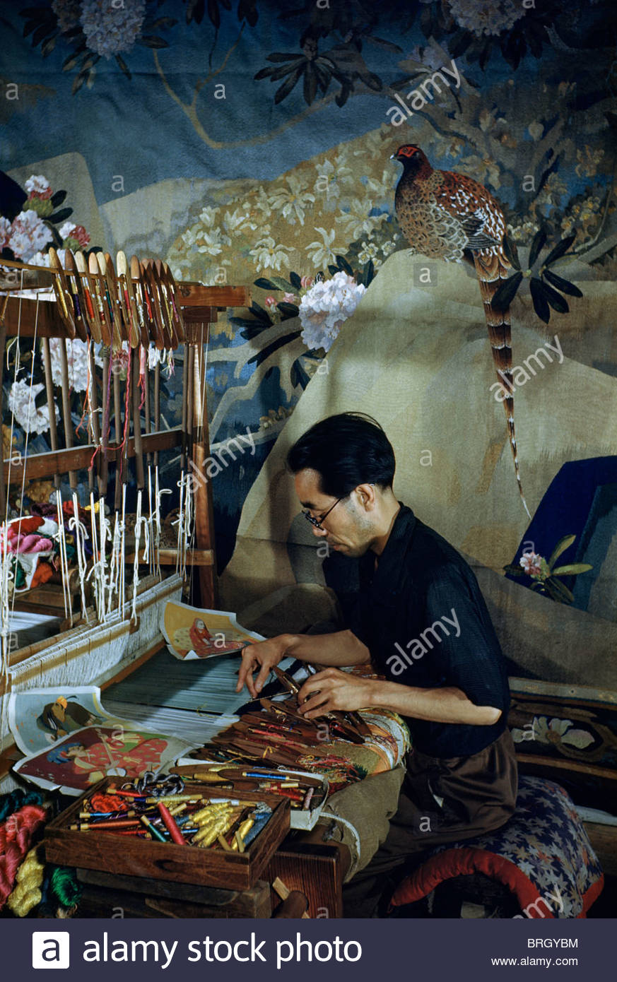 An artist hand-weaves a silk tapestry. - Stock Image