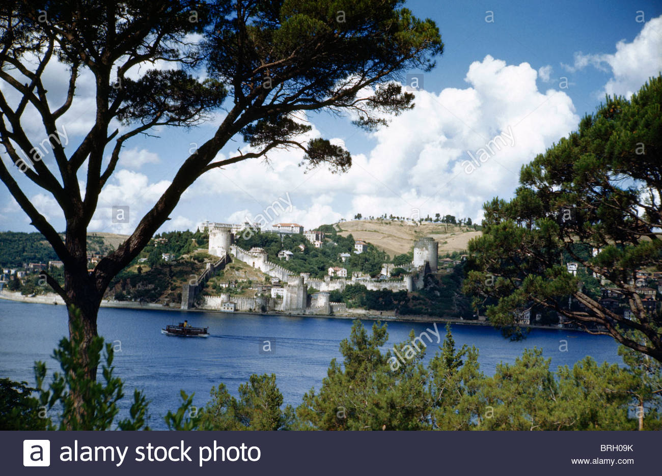 A boat plies the Bosporus near the ruins of Rumeli Hissar fortress. - Stock Image