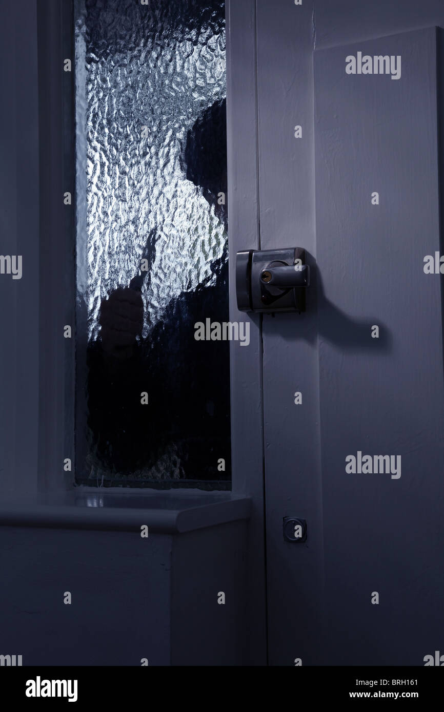 Figure of someone outside looking through an opaque glass window, holding a knife - Stock Image
