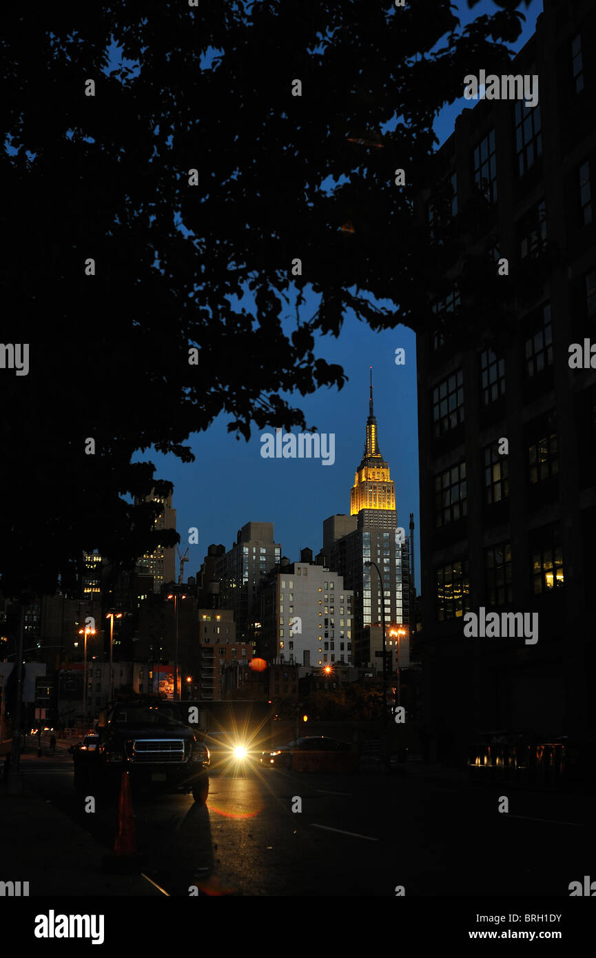 New York landmark the Empire State Building gold lights top and spire lit up at night seen framed by trees New York - Stock Image