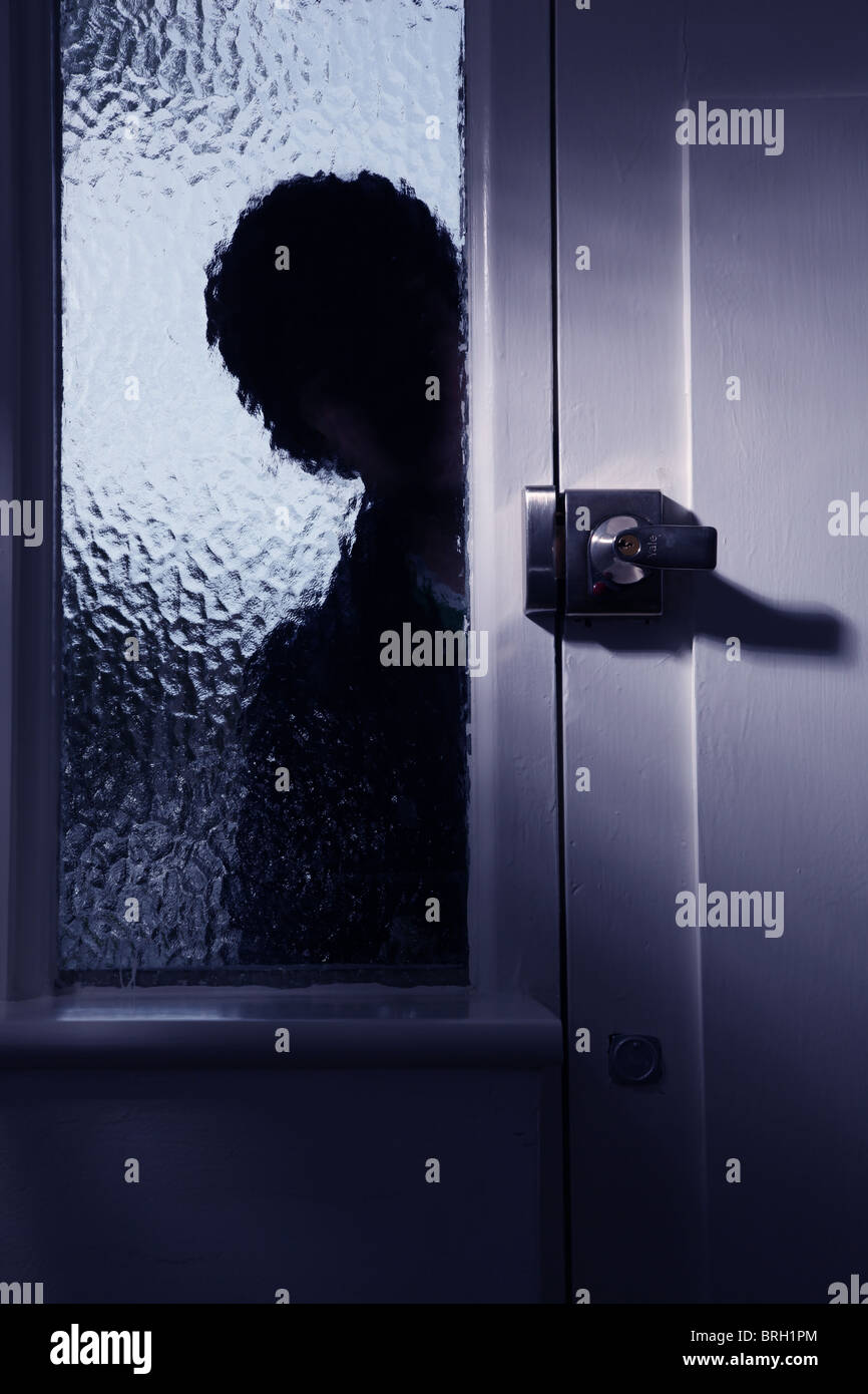 Silhouette male intruder looking through an opaque window next to a front door Stock Photo