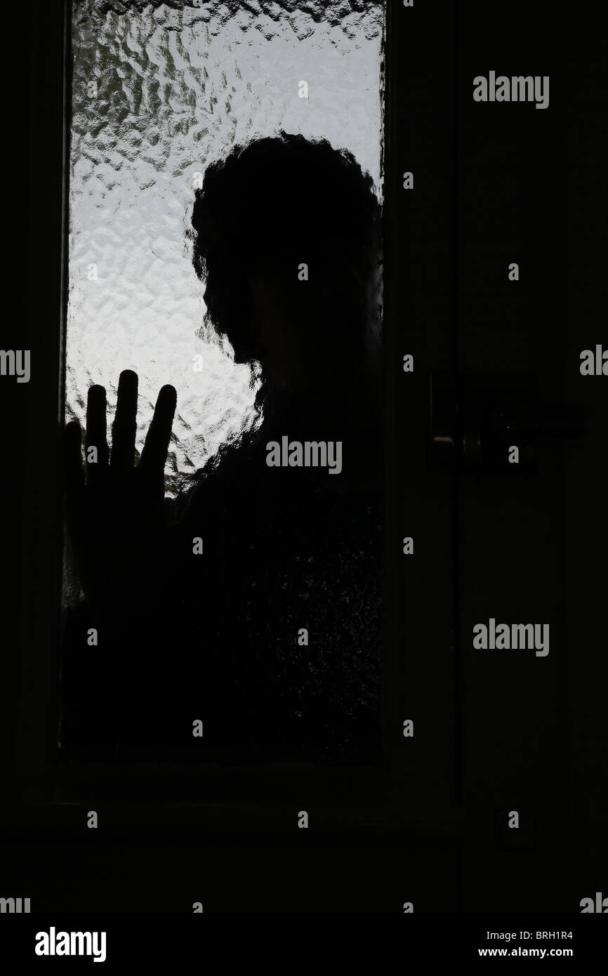 Silhouette male intruder looking through an opaque window next to a front door - Stock Image