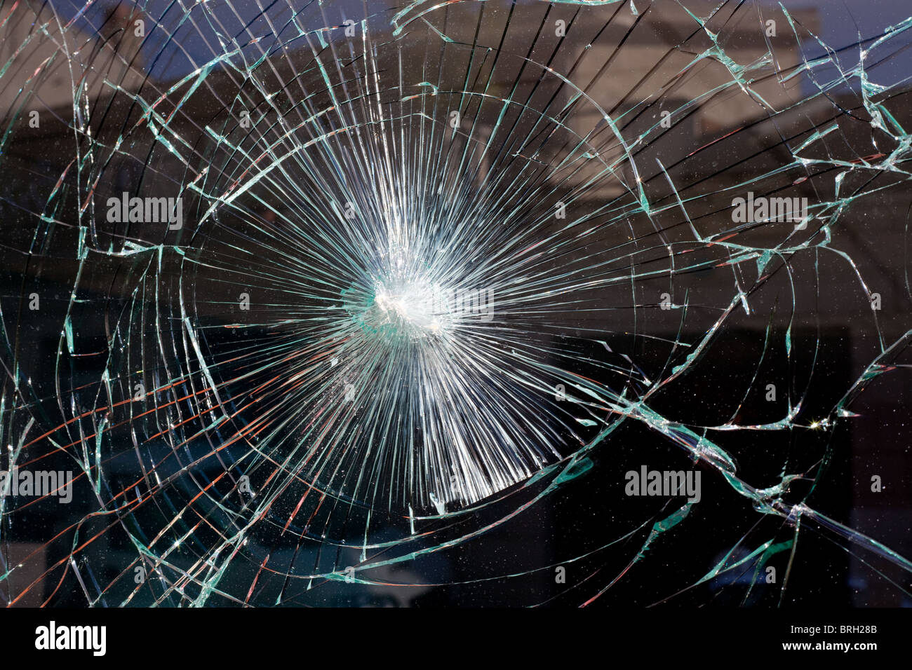 broken window glass like a spider web with building reflection - Stock Image