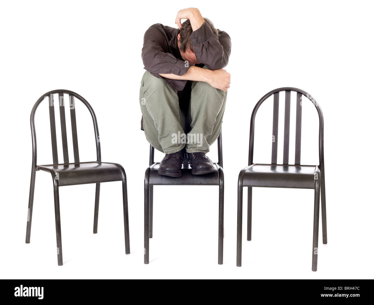 very anxious and sad man hiding himself and alone - Stock Image