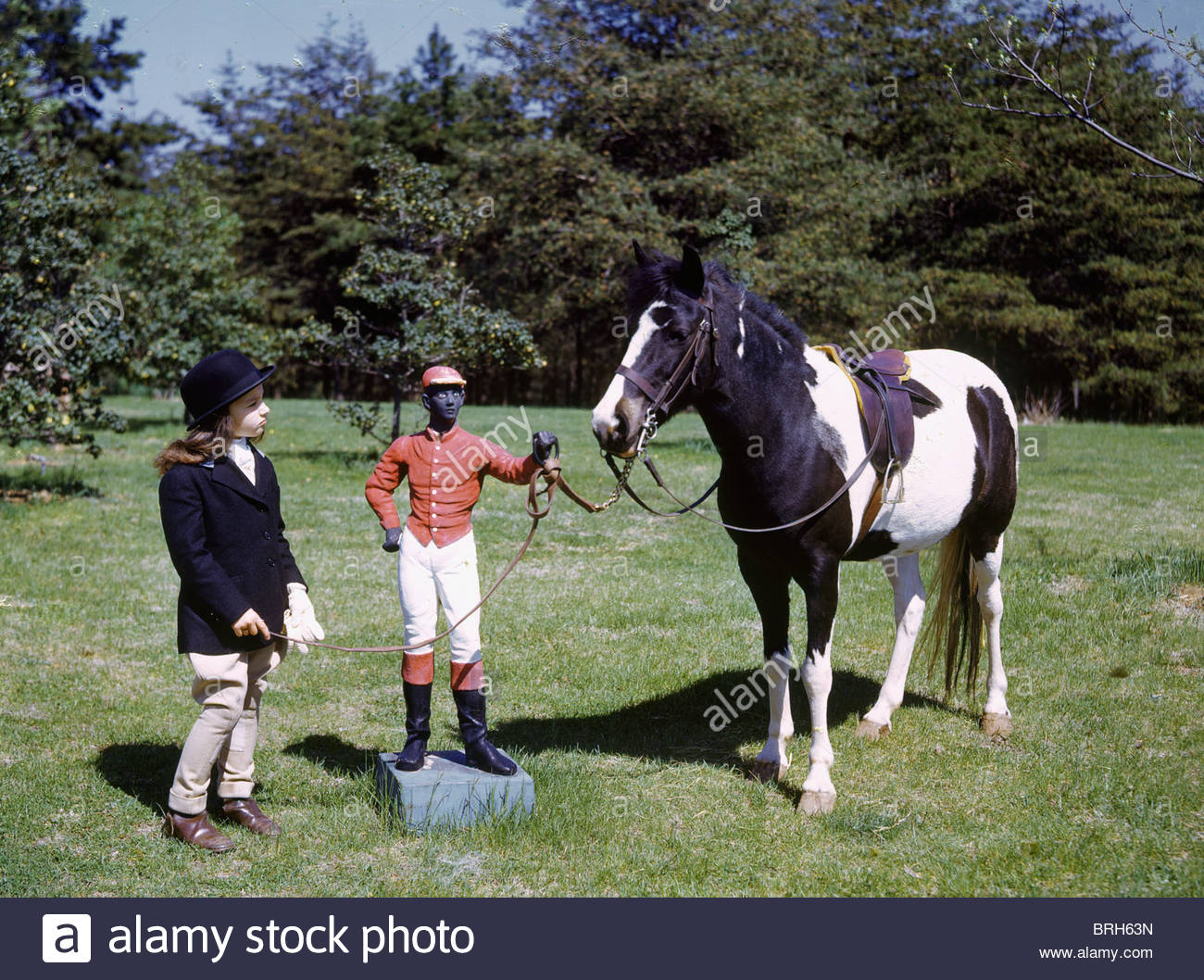 A young girl and her horse at a cast iron hitching post