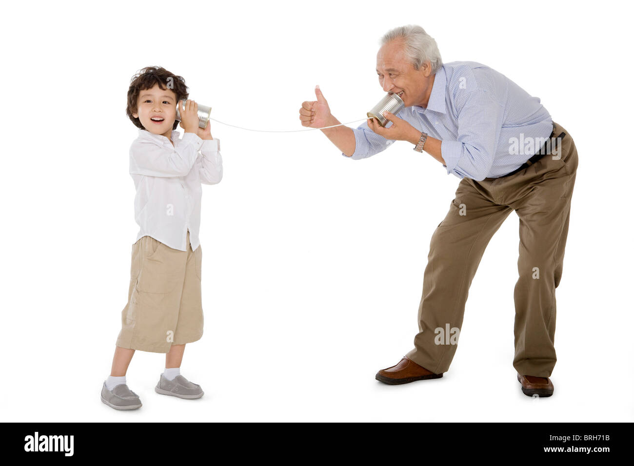 Grandfather and grandson playing with a tin-phone - Stock Image