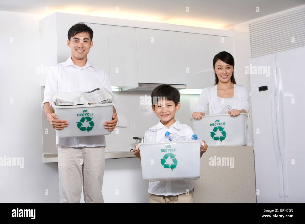 Family holding recycling boxes in kitchen - Stock Image