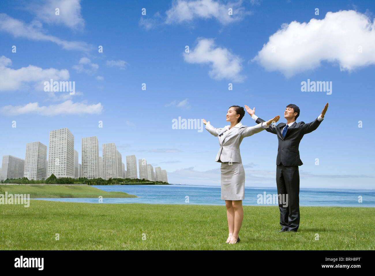 Businesspeople with their arms outstretched in an urban park - Stock Image