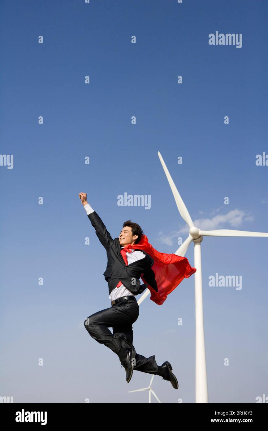 Everyday hero in front of wind turbines - Stock Image