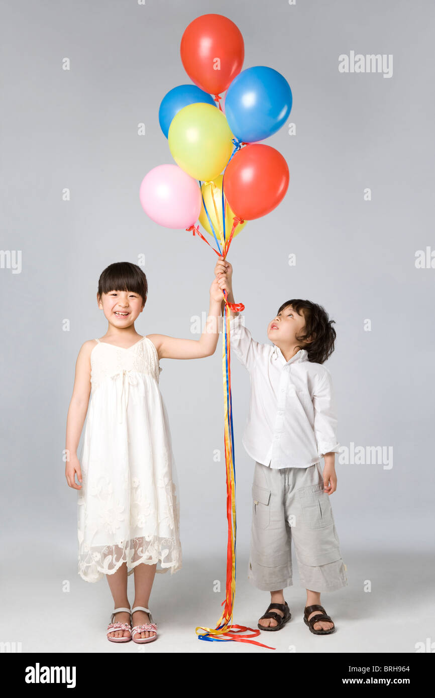 Children holding multi-colored balloons - Stock Image