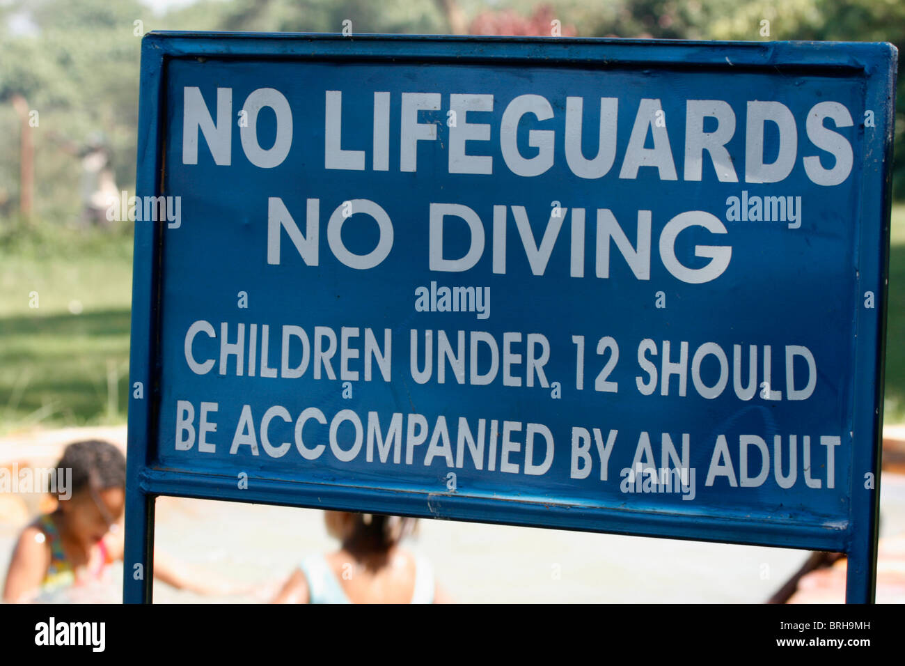 Sign at a swimming pool warning that there are no lifeguards and that children under 12 should be accompanied by - Stock Image