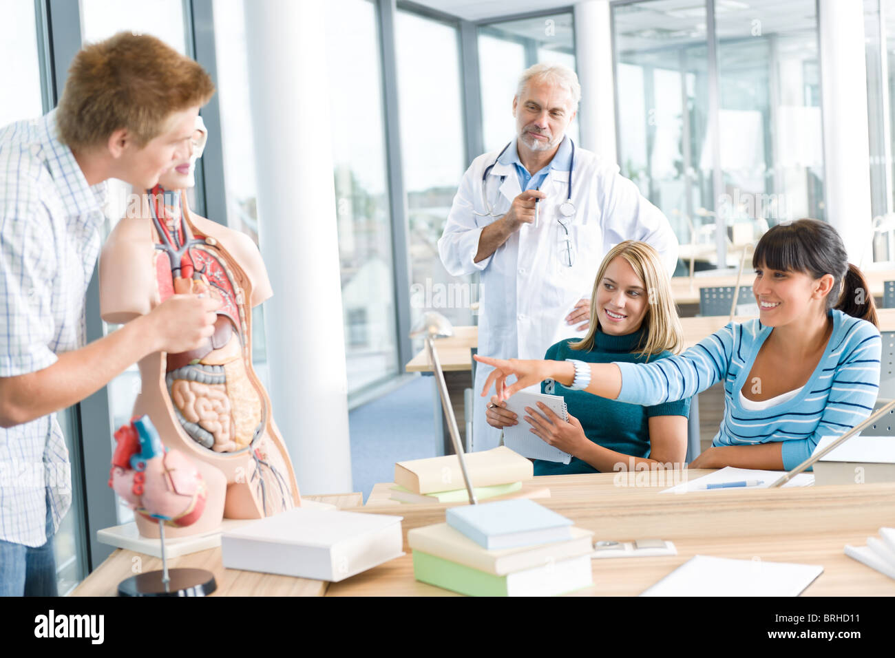 University - medical students with professor and human anatomical model in classroom - Stock Image