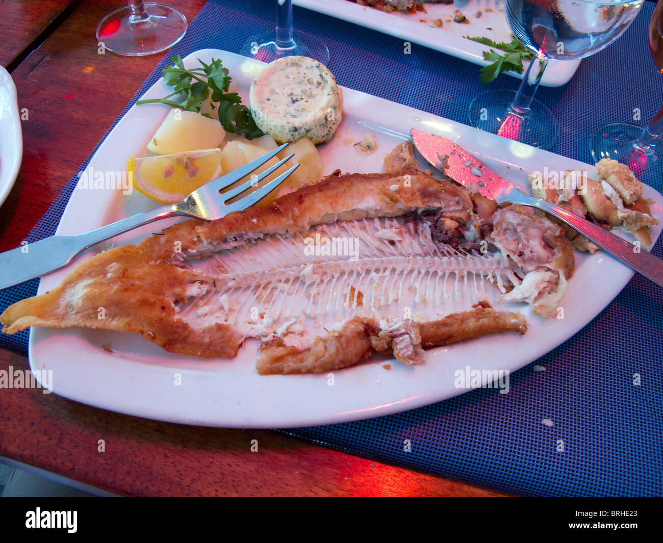 An eaten meal of Sole Grille with garnish and knife and fork at a French restaurant - Stock Image