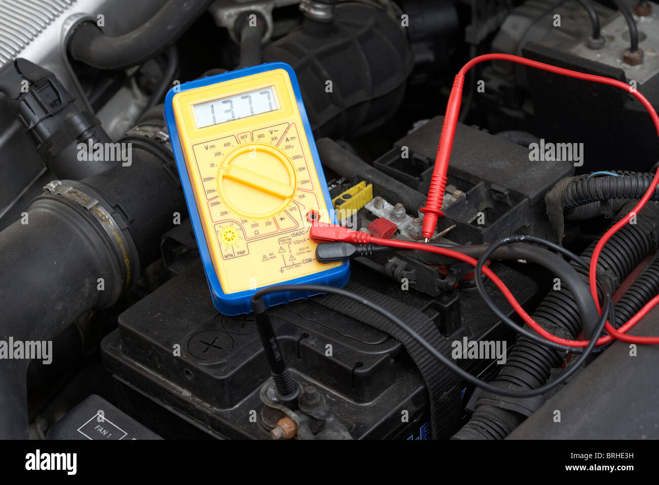 measuring voltage of a car battery using a multimeter - Stock Image
