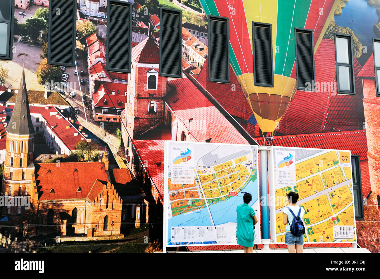 Shanghai World Expo 2010, China. Visitors looking at site map and mural - Stock Image