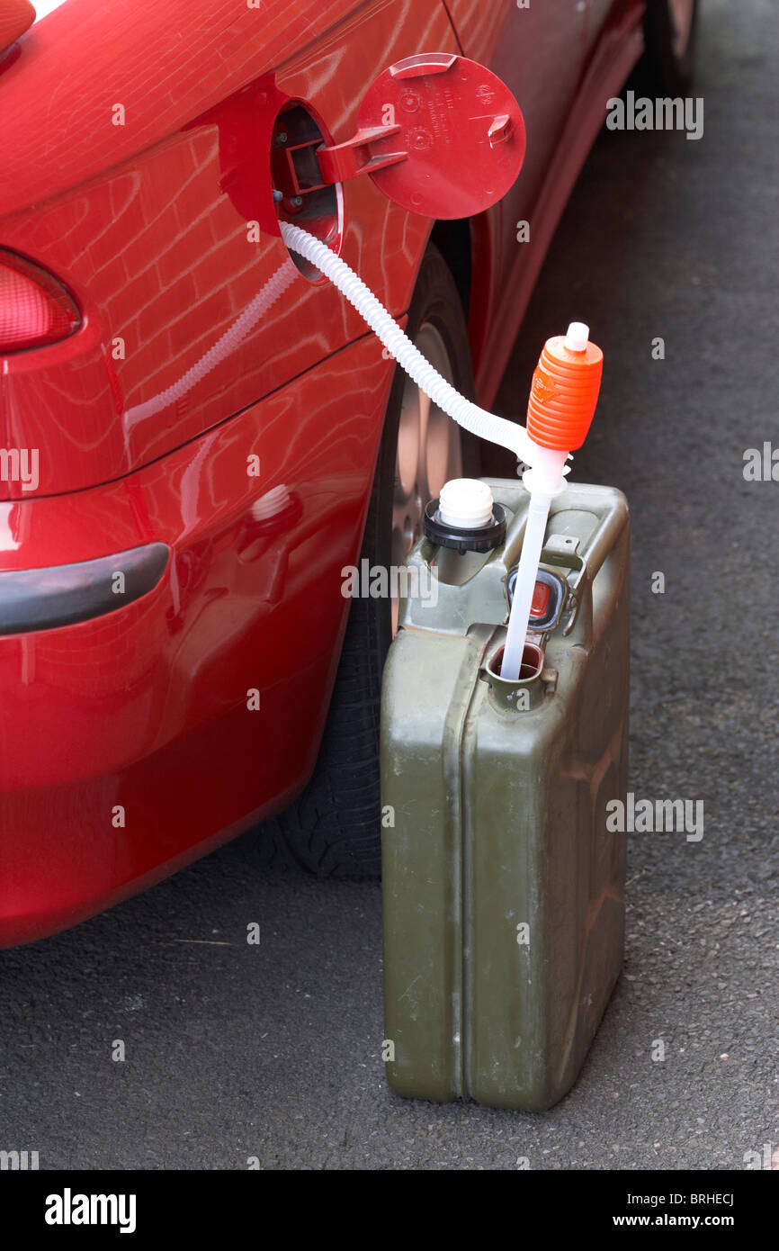 refueling car from fuel jerry can with syphon - Stock Image