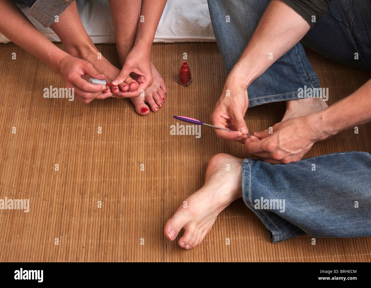woman painting her toenails with red nail-varnish while man cleans his nails with file - Stock Image