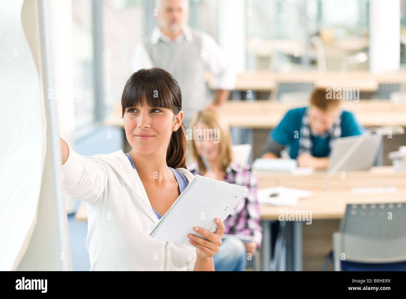 High school - three students with mature professor in classroom - Stock Image