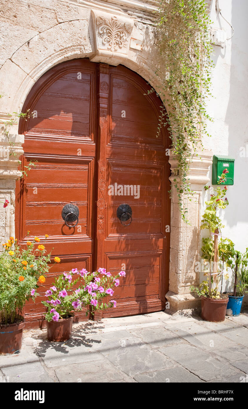 Impressive double wooden doors and limestone arched facade Rethymno Crete Greece - Stock Image
