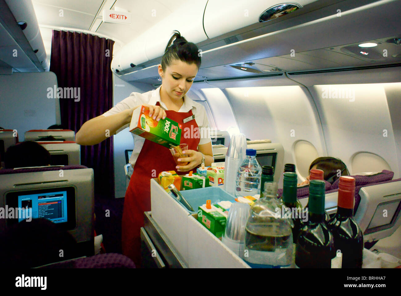 Long haul flight air stewardess with food drinks aisle trolley on overnight Virgin Atlantic aircraft serving drink - Stock Image