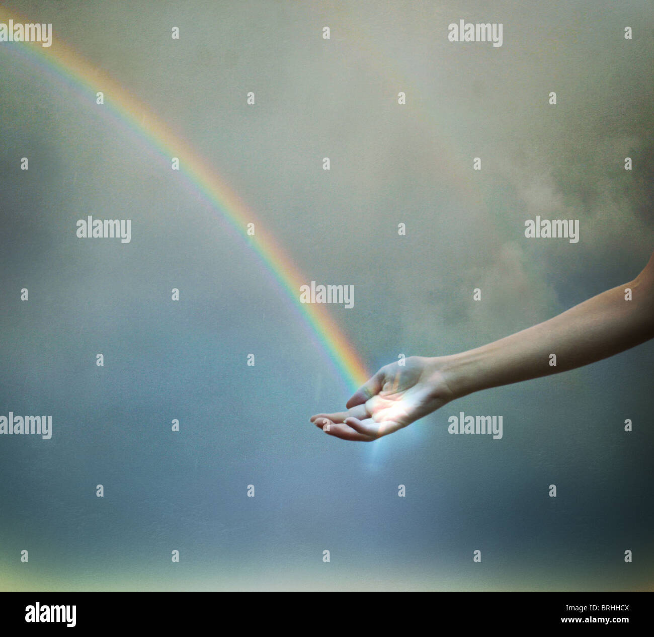 rainbow touching a hand - Stock Image