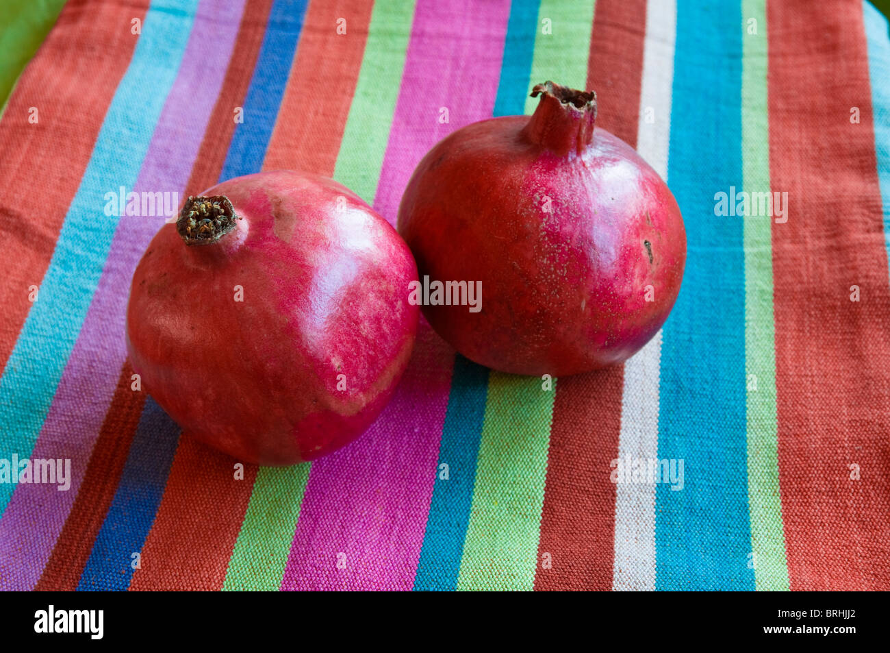 Pomegranate fruits with a colourful stripy cotton cloth background. - Stock Image