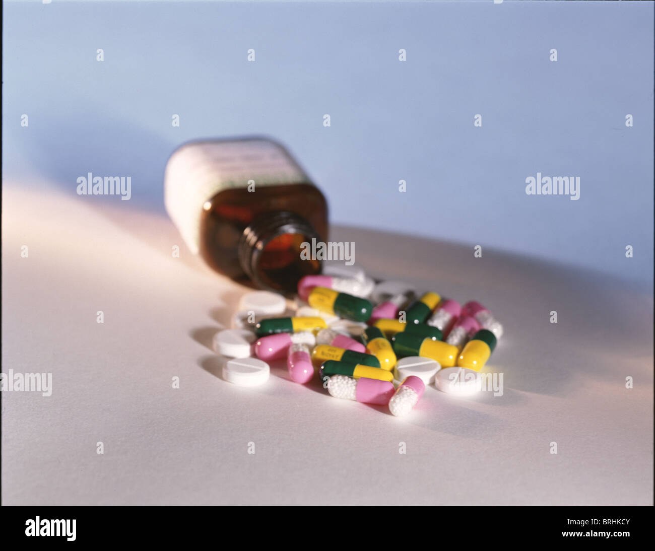 Bottle open on its side with pills spilled out - Stock Image