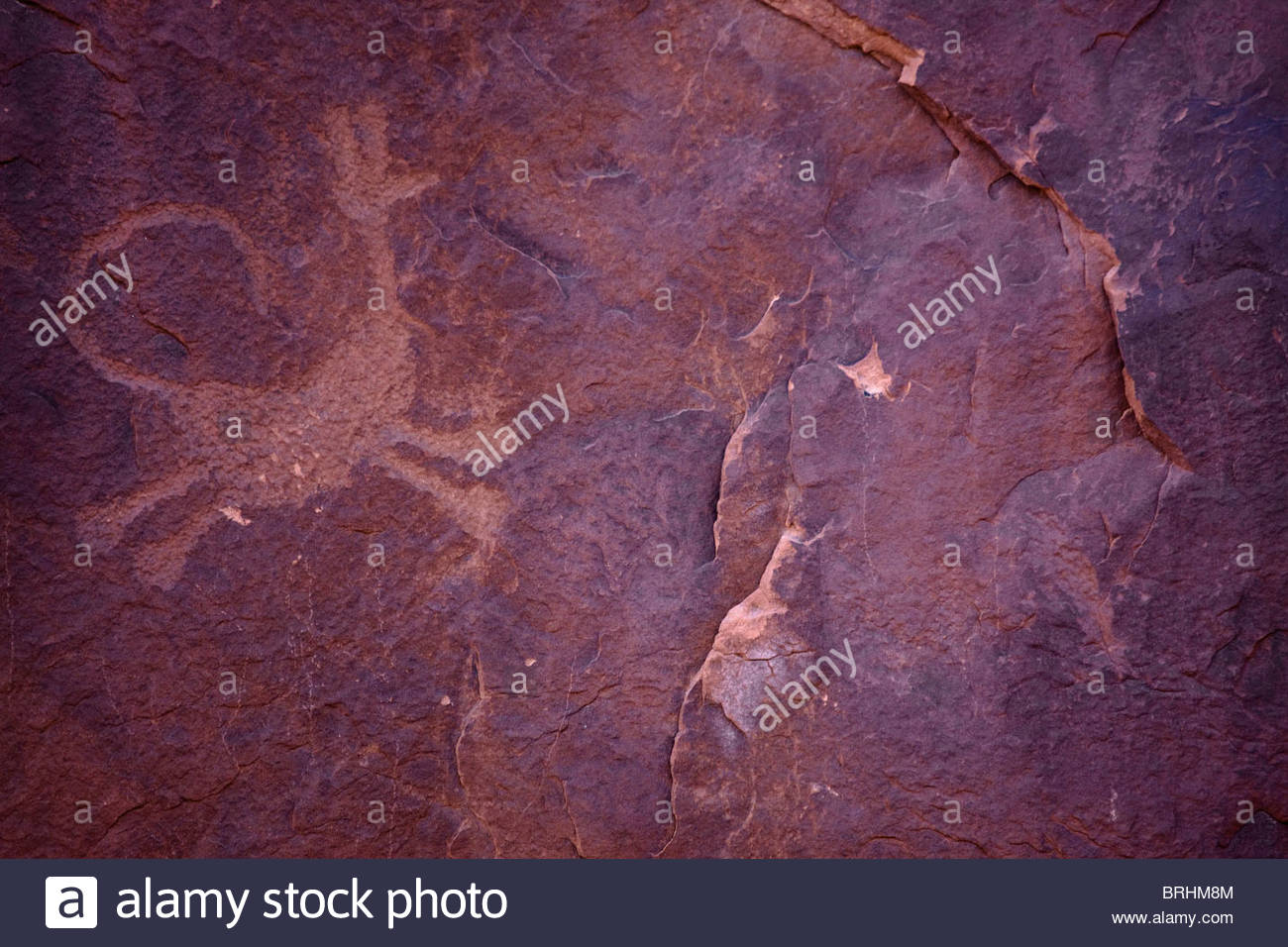 An ancient piece of rock art that resembles an animal figure running. - Stock Image