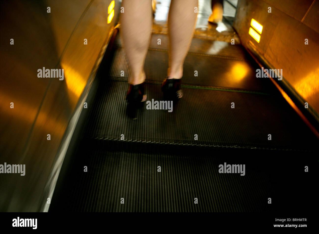 woman legs standing on escalator in underground - Stock Image