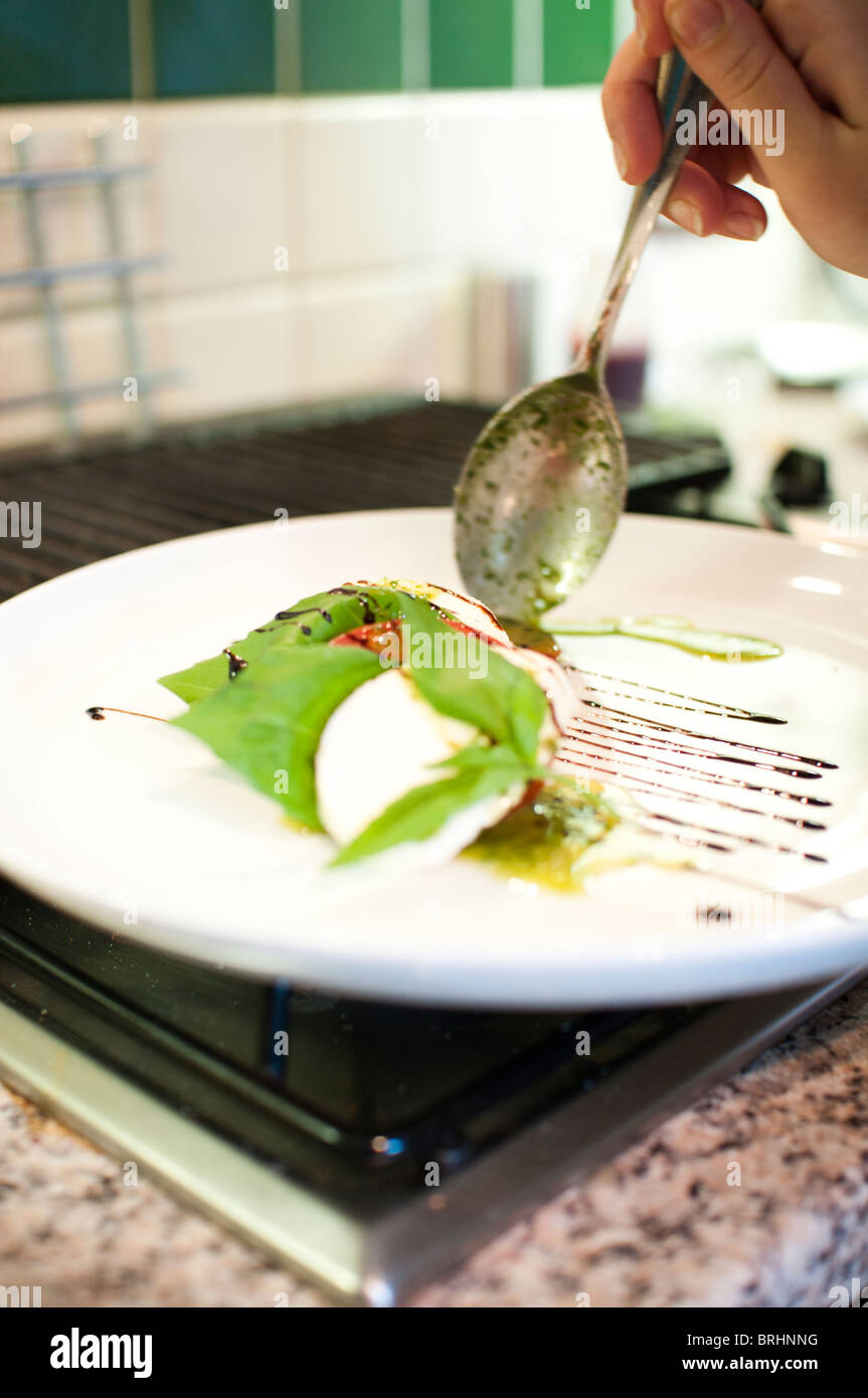 Posh salad with dressing being applied - Stock Image
