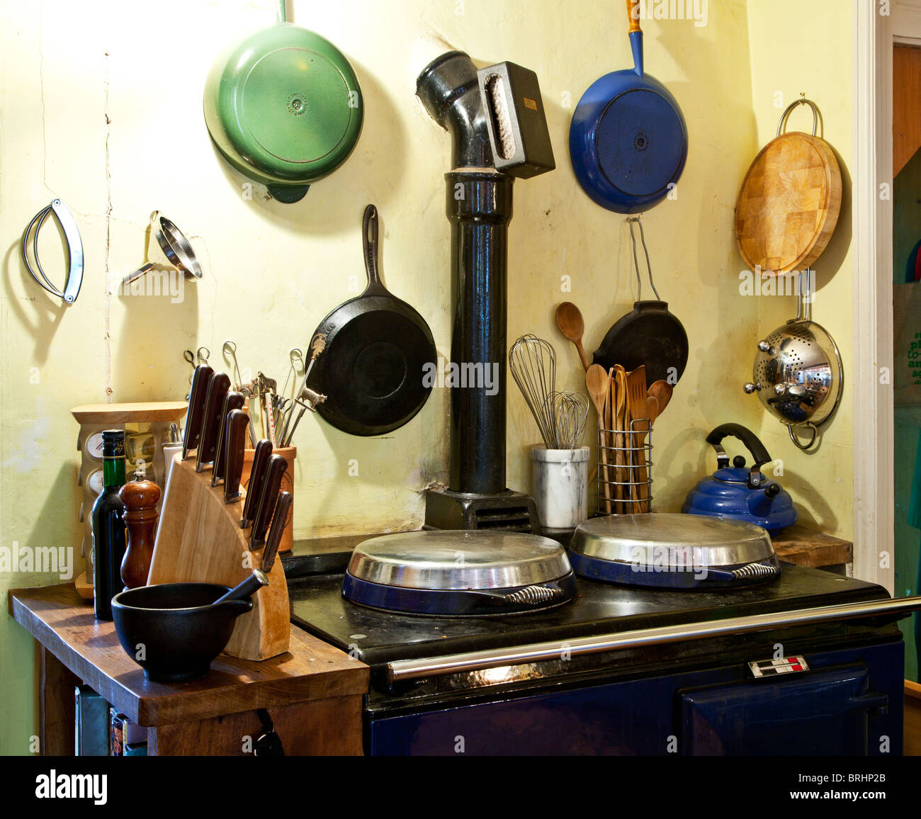 A corner of an English country style kitchen with an Aga or range and pots and pans and cooking utensils Stock Photo