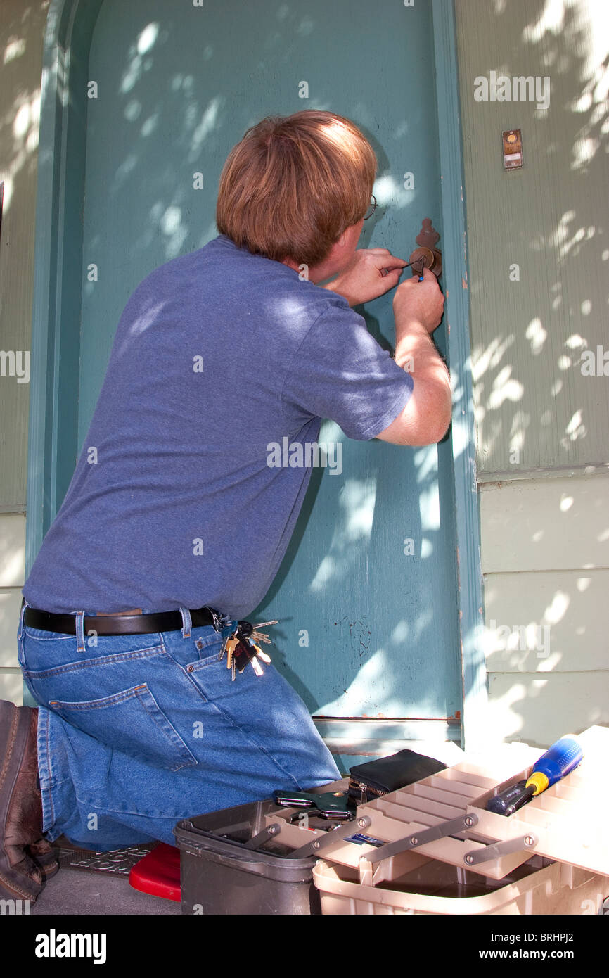 Locksmith unlocks lock on house front door - Stock Image