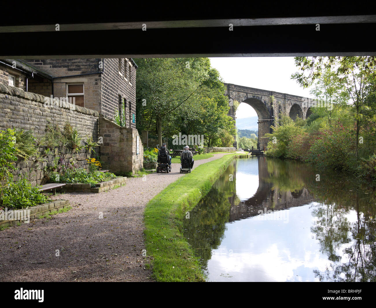 Two men on invalid vehicles on canal towpath, Uppermill, Saddleworth,Oldham, England, UK. - Stock Image