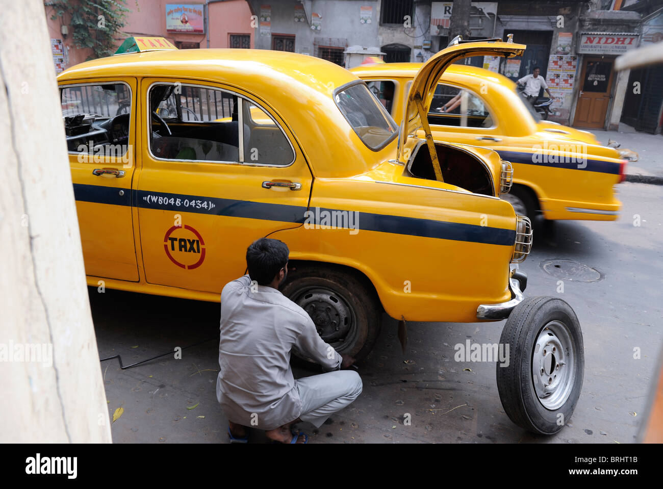 South Asia India Calcutta Kolkata , taxi driver repair a cab with flat tyre , Ambassador car which is based on the - Stock Image