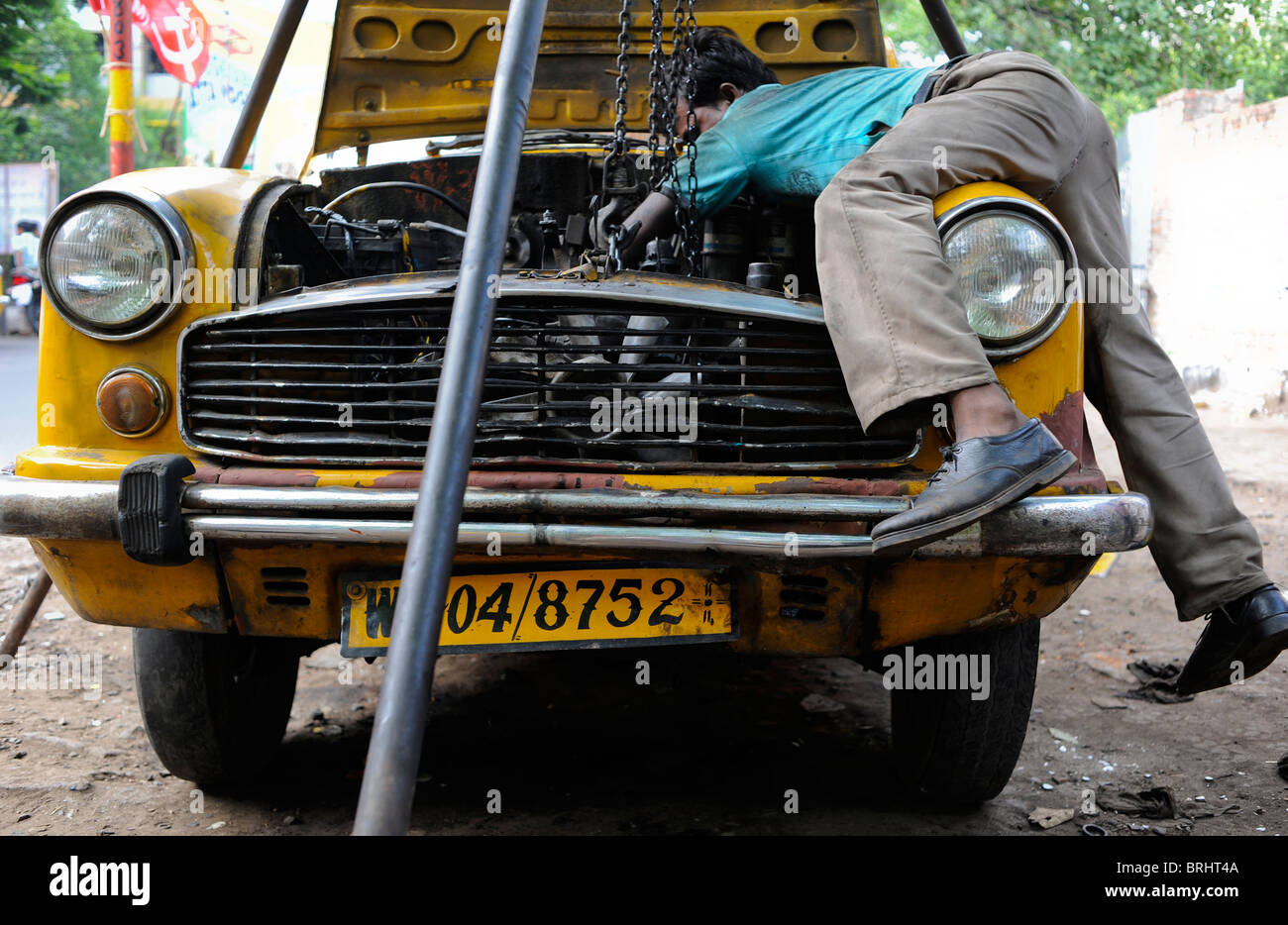 INDIA Calcutta Kolkata , mechanic repair a yellow cab , a HM Ambassador car , which is based on Oxford Morris, in - Stock Image