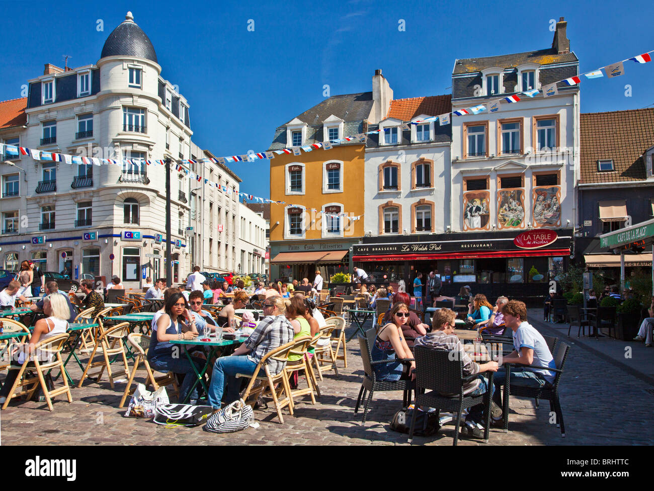 People enjoying the sunshine and chatting at an outdoor cafe in the Place Dalton in Boulogne, France - Stock Image