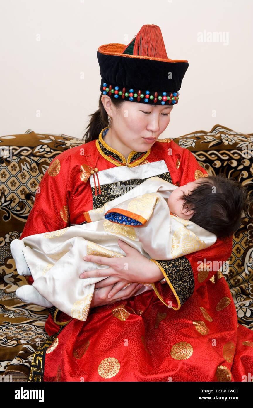 Mongolian woman rocks her baby to sleep - Stock Image