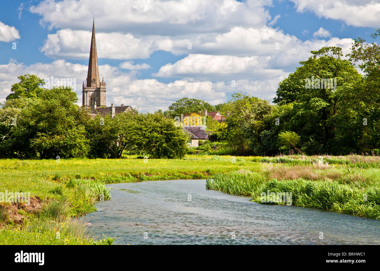 Summer view across meadow and River Windrush to St John the Baptist Church in Cotswold town of Burford, Oxfordshire, - Stock Image